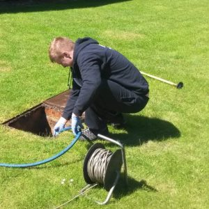 Unblocking a drain in a customers back garden manhole